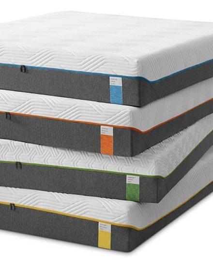 cztery szaro-białe materace Tempur leżące jeden na drugim – każdy z metką w innym kolorze