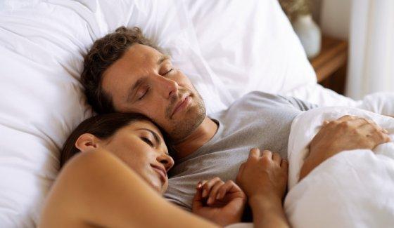 para śpi w łóżku, mężczyzna leży na plecach, kobieta śpi na boku